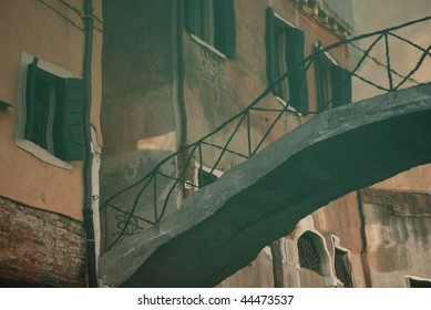 Reflection of an old bridge over a canal in Venice