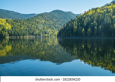 Reflection on the Yenisei River, autumn view. Sayano-Shushenski Nature Biosphere Reserve. Wild place in Siberia, Krasnoyarsk region.