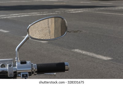 reflection of a pavement in the mirror of a motorcycle