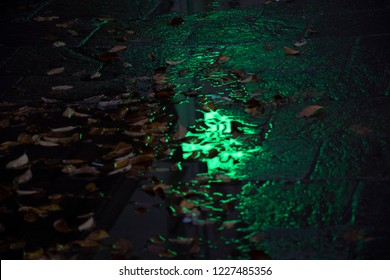 Reflection of pharmacy sign in water paddle in rainy autumn night. Slippery danger caution and first aid concept. Abstract background. Selective focus.
