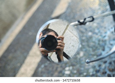 reflection of photographer with camera in round mirror