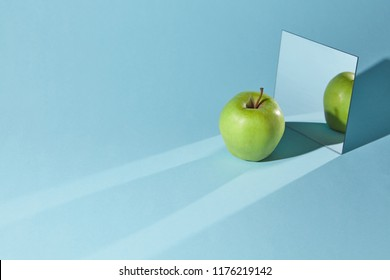 Reflection of a piece of a green apple and shadow from apple in a mirror. Diagonal long shadows from apple and mirror on the blue table surface.