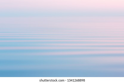 Reflection of the pink sunset in the flowing water surface with a white haze. Abstract seascape background in pastel sweet colors with motion blur filter. Space for copy and design.