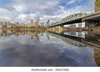 Reflection of Portland Oregon downtown city skyline by Hawthorne Bridge on Willamette River daytime