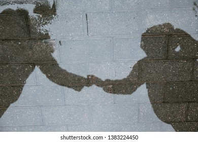 Reflection in a puddle of boy and girl holding hands on the road.