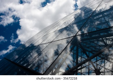 A Reflection of puffy white clouds in a clear glass building.