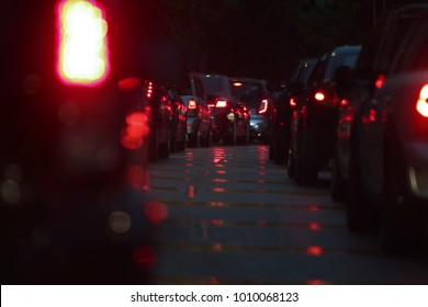 reflection of the red brake light on a wet road when the street is crowded at night time
