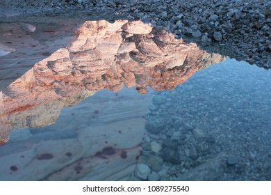 reflection of red rocks in a canyon pool