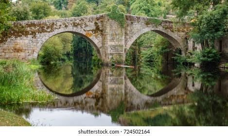 Reflection of river and medieval bridge in Allariz, Orense, Galicia, Spain