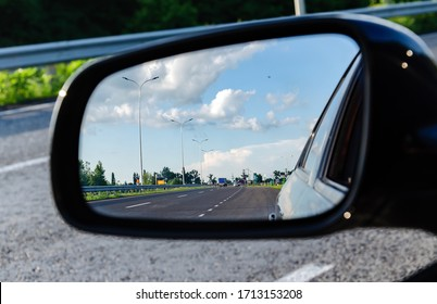 reflection of the road in the car mirror, with the sky and clouds, warm summer evening, close-up