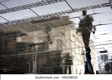 Reflection shadow of a man walking in the city pedestrian zone just after the rain