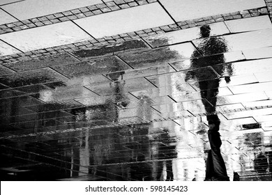 Reflection shadow of a man walking in the city pedestrian zone just after the rain, in black and white