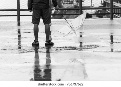 Reflection shadow of a young man standing with transparent-umbrella on the floor after rain.in black and white, with reflections