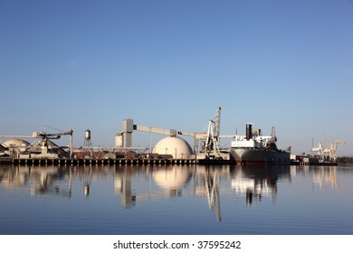 Reflection of ship and industrial shipping equipment at port of Stockton, California.