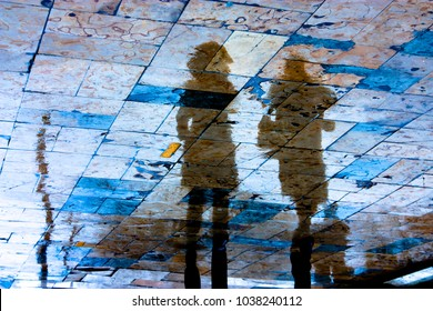 Reflection silhouette of two young women walking city sidewalk on a rainy day with vibrant colors