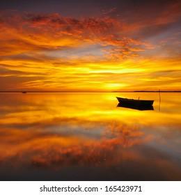 Reflection of Single Boat with Burning Sky During Sunrise/Sunset