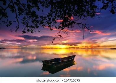 Reflection of Single Boat During Sunrise under the Tree