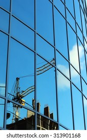 reflection of the sky in the glass windows of the crane construction