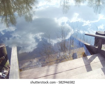 The reflection of sky and trees in the lake in the early spring