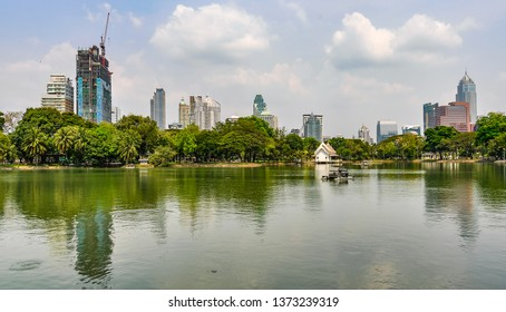 Reflection of skyscrapers in Lumpini Park in the city of Bangkok in Thailand