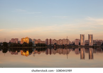 Reflection of skyscrapers in the water. The city on the lake. Kiev, Ukraine. Sunset on the pond, city landscape and nature together.