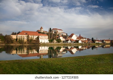 Reflection of the Slovenian old town Ptuj on the surface of the river. Top on the hill is a old castle covered with red roof. Dramatic sky with clouds,  quiet Drava river .