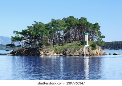 Reflection of small lighthouse in beautiful blue sea surface in front of port of Rab town on Croatian seacoast, surrounded with old green pine tree