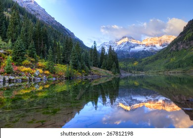 Reflection of Snow capped Maroon Bells in fall, at sunrise.