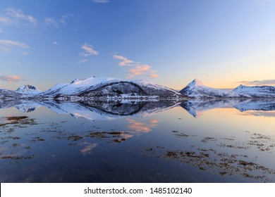Reflection of snow-covered mountains in the fjord on Senja Island, Troms County, Norway