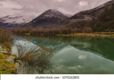 Reflection of snowy mountains within Noguera de Tor river, Barruera, Vall de Boi, Lleida, Catalonia, Spain