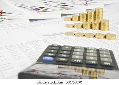 Reflection step pile of gold coins in calculator on finance account have pile of paperwork as background. Stack of paperwork is high as work hard. Business and finance concepts rich and successful.
