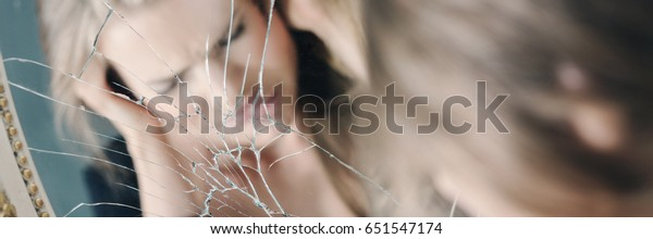 Reflection of stressed woman holding her head in broken mirror