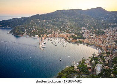 Reflection of sun rays in the water Ligurian sea at the sunset. Panorama of harbor with moored white yachts and boats in Santa Margherita Ligure near Portofino, Italy.