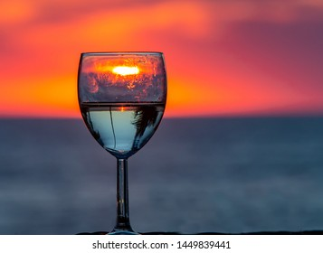 Reflection of sun through glass of wine at sunset