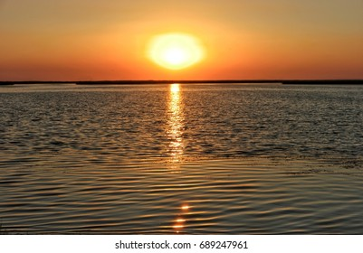 The reflection of the sun in the water, the sunset over the sea bay