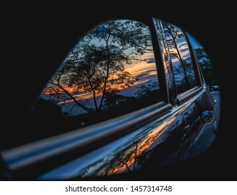 Reflection of the sunset in the car mirror. Bright reflection of the sunset in the car mirror