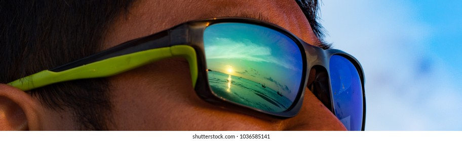 Reflection of sunset scene in green sunglasses