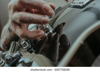 Reflection of Tattooed Hand Playing Guitar