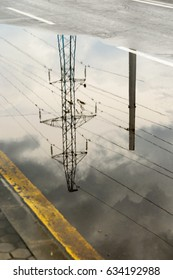Reflection of transmission tower in large puddle on an overcast day, in black and white, for themes of electricity and power, infrastructure, juxtaposition