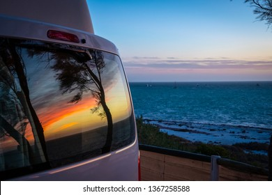 Reflection of tree silhouettes on campervan window in front of Indian Ocean in Australia