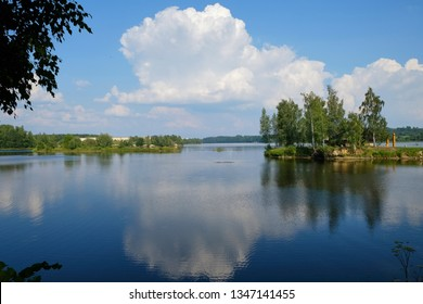 Reflection of trees and clouds in water. Not the big island in the lake on which among trees stands the wooden house.