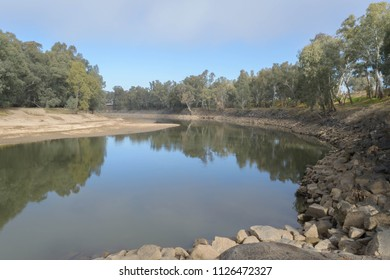 reflection of trees on a shallow murrumbidgee river in the country on a sunny day with clouds in the sky