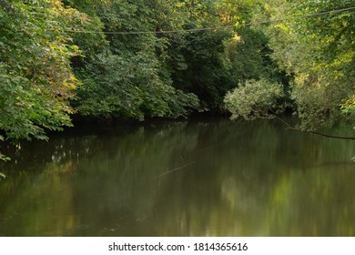 Reflection of trees over a river on the start of autumn