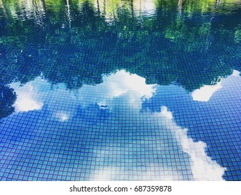 Reflection of trees and sky to swimming pool