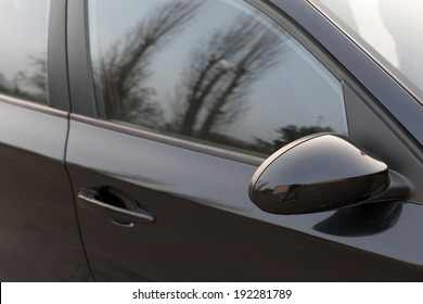 Reflection of trees in the window of a car