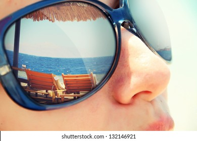 Reflection of a tropical resort in sunglasses