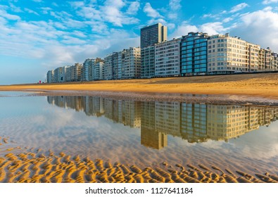 Reflection of the urban skyline of Ostend in the North Sea with its waterfront and apartment buildings, Belgium, Europe.