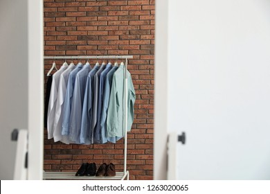 Reflection of wardrobe rack with men's clothes near brick wall in mirror at home. Space for text