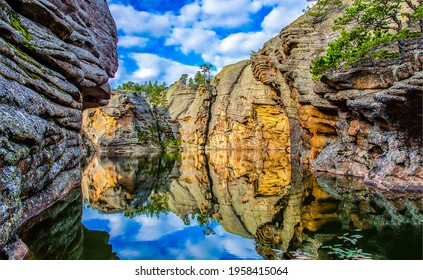 Reflection of water in a river canyon among the mountains. Cliffs are reflected in the water. Reflection in water scene
