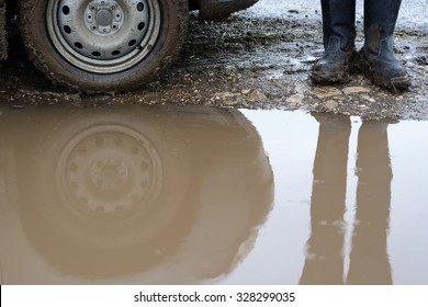 Reflection wheel car in a muddy puddle and men's feet in shoes